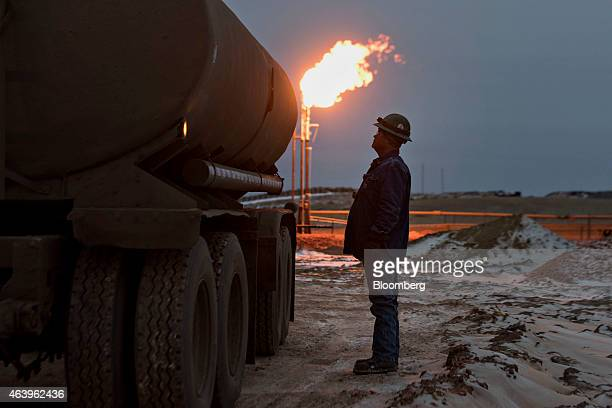A gas flare burns as Jim Zumwalt a driver with Black Hills Trucking monitors a water tank while loading saltwater from an oil well storage tank near...