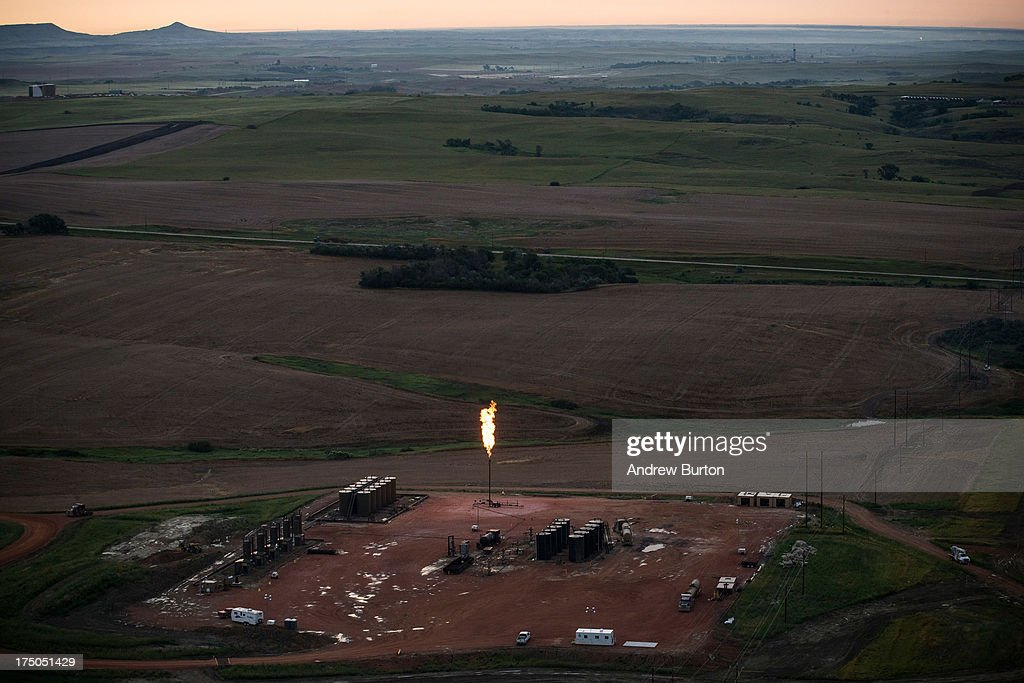 A gas flare is seen in an aerial view in the early morning hours of July 30, 2013 near Watford City, North Dakota. Gas flares are caused when pressure release valves release excess natural gas from an oil pumpjack; the gas is then ignited to burn off the fumes. North Dakota has seen a boom in oil production thanks to new drilling techniques including horizontal drilling and hydraulic fracturing.