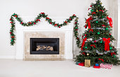 Natural Gas Fireplace with fully decorated Christmas tree in living room of home during holidays