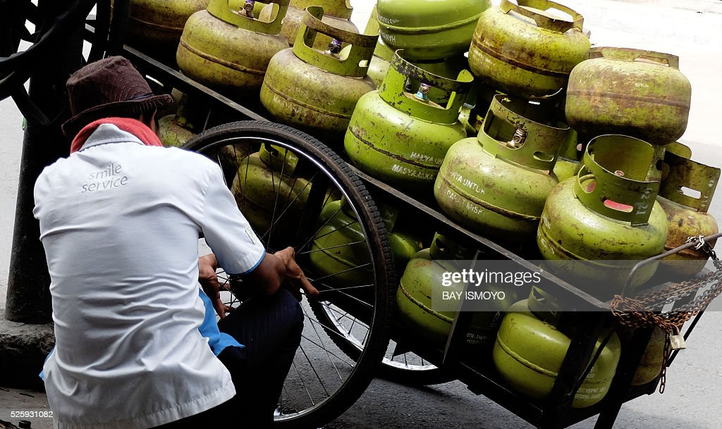 A gas merchant repairs his damaged cart wheel in Jakarta on April 29, 2016 during his door to door service. Indonesia's economy may recover more slowly than expected as the expansion of the manufacturing industry, which the government hopes will propel growth amid low private consumption, remains weak. / AFP / BAY