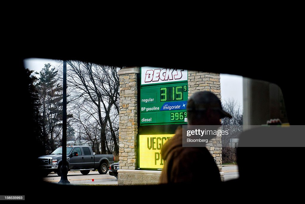 Gas prices are displayed beyond customer Lester Behrends as he fills his truck with fuel at a gas station in Princeton, Illinois, U.S., on Tuesday, Dec. 18, 2012. Retail gasoline in the U.S. fell to the lowest level in a year as refineries restored production and stockpiles rose to an eight-month high, blunting criticism of President Barack Obama's energy policies. Photographer: Daniel Acker/Bloomberg via Getty Images
