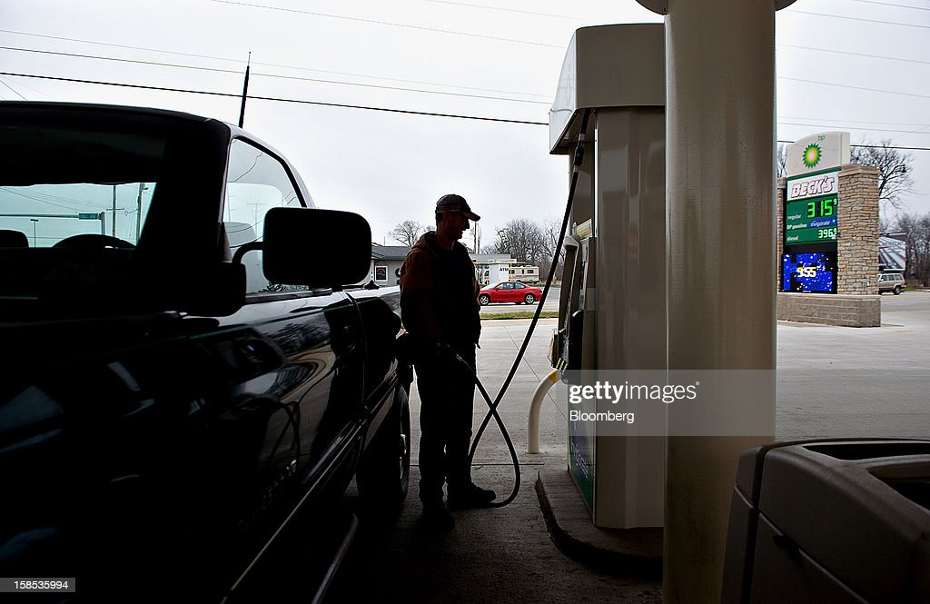 Gas prices are displayed, right, as customer Lester Behrends fills his truck with fuel at a gas station in Princeton, Illinois, U.S., on Tuesday, Dec. 18, 2012. Retail gasoline in the U.S. fell to the lowest level in a year as refineries restored production and stockpiles rose to an eight-month high, blunting criticism of President Barack Obama's energy policies. Photographer: Daniel Acker/Bloomberg via Getty Images