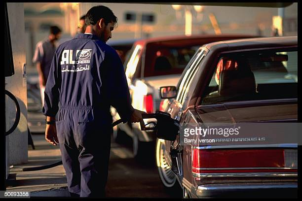 Gas station attendant filling up Americanmade Mercury Grand Marquis LS car