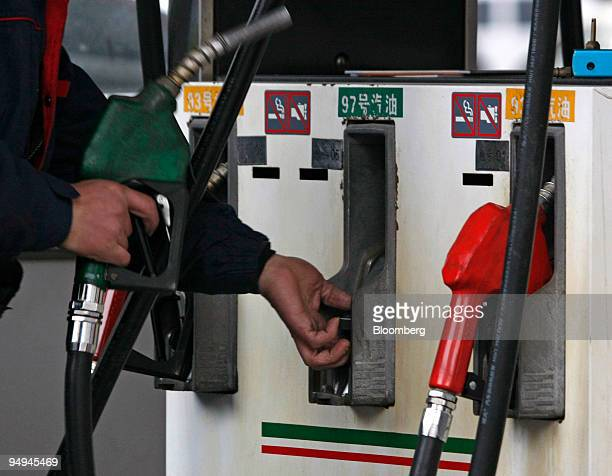 A gas station attendant operates a gas pump at a China Petroleum and Chemical Corp gas station in Shanghai China on Sunday Feb 15 2009 China the...