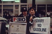Gas station attendants peer over their 'Out of gas' sign in Portland on day before the state's requested Saturday closure of gasoline stations Image...