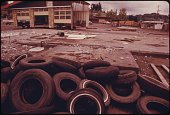 Gas station that had no fuel allocation and was closed during the gas crisis of 19731974 a pile of tires in the foreground the empty building in the...
