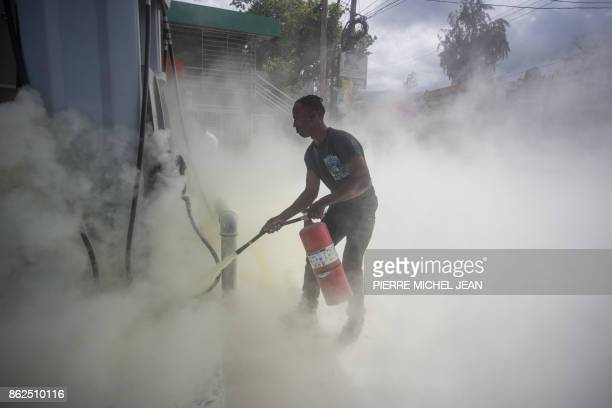 A gas station worker puts out a fire set by demonstrators marching against the government of Haitian President Jovenel Moise in PortauPrince on...