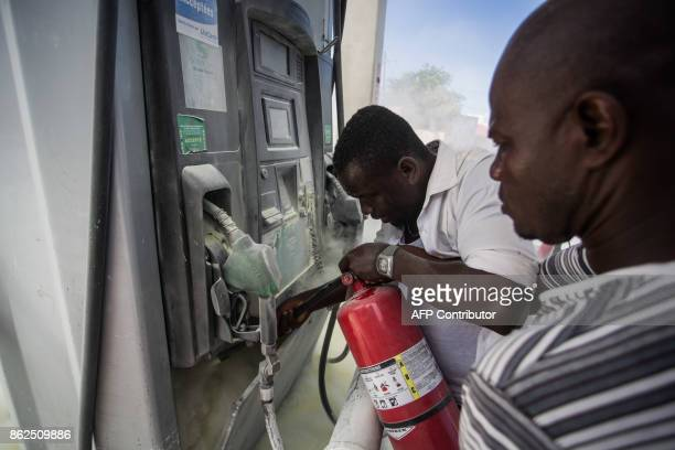 Gas station workers put out a fire set by demonstrators marching against the government of Haitian President Jovenel Moise in PortauPrince on October...