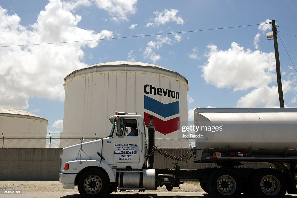 A gas tanker passes a Chevron petroleum storage tank at Port Everglades May 24 2004 in Fort Lauderdale Florida The port is a major petroleum storage...