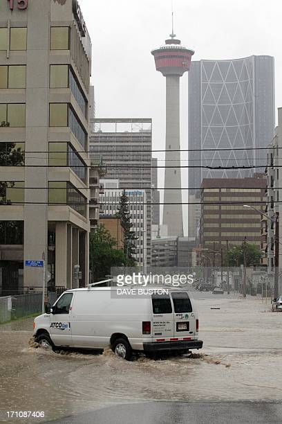 A gas truck drives through rising waters before the Calgary Tower in Calgary Alberta Canada June 21 2013 Flooding forced the evacuation on Friday of...