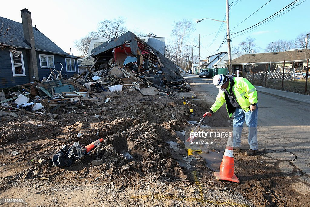 A gas worker marks a gas line in front of homes damaged by Superstorm Sandy on January 4, 2013 in the New Dorp area of the Staten Island borough of New York City. More than two months after the storm, Congress passed legislation today that will provide $9.7 billion to cover insurance claims filed by people whose homes were damaged or destroyed by Sandy.