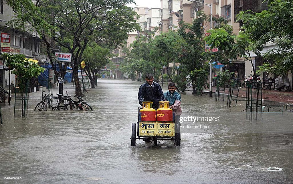 Gas worker moving with Gas-cylinder during the heavy rain fall in Mumbai on August 1, 2005 in Mumbai, India.