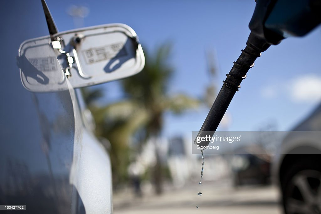 Gasoline drops from the end of the nozzle as an attendant finishes filling the tank of a vehicle at a Petroleo Brasileiro SA (Petrobras) station in Rio de Janeiro, Brazil, on Thursday, Jan. 31, 2013. State-controlled oil company Petrobras announced earlier this week that it would raise gasoline and diesel prices by 6.6 percent and 5.4 percent, respectively. Photographer: Dado Galdieri/Bloomberg via Getty Images