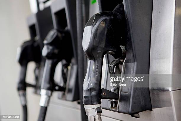 Gasoline nozzles hang on a fuel pump at a Hess Corp gas station in Washington DC US on Monday Jan 26 2015 Hess Corp is expected to report...