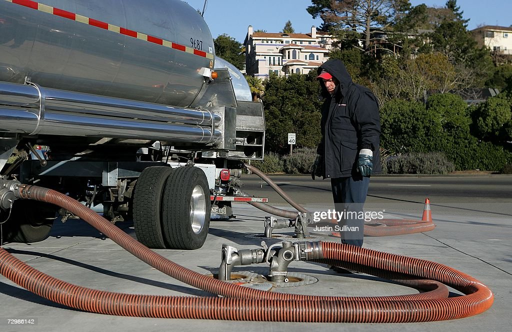 A gasoline tanker truck driver looks on as he fills underground tanks with gasoline at a Chevron service station January 12 2007 in Greenbrae...