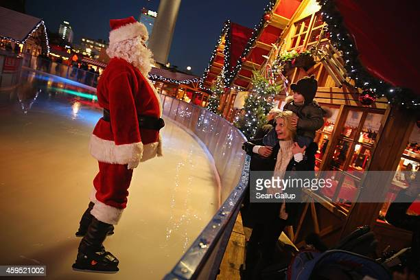 Gaspard and his mother Anne get a visit from Santa Claus at an iceskating rink at the Christmas market at Alexanderplatz on the market's opening day...