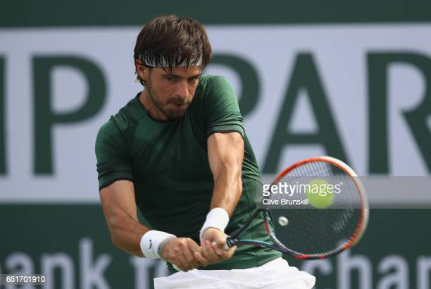 Gastao Elias of Portugal plays a backhand during his first round match against Kyle Edmund of Great Britain during day five of the BNP Paribas Open...