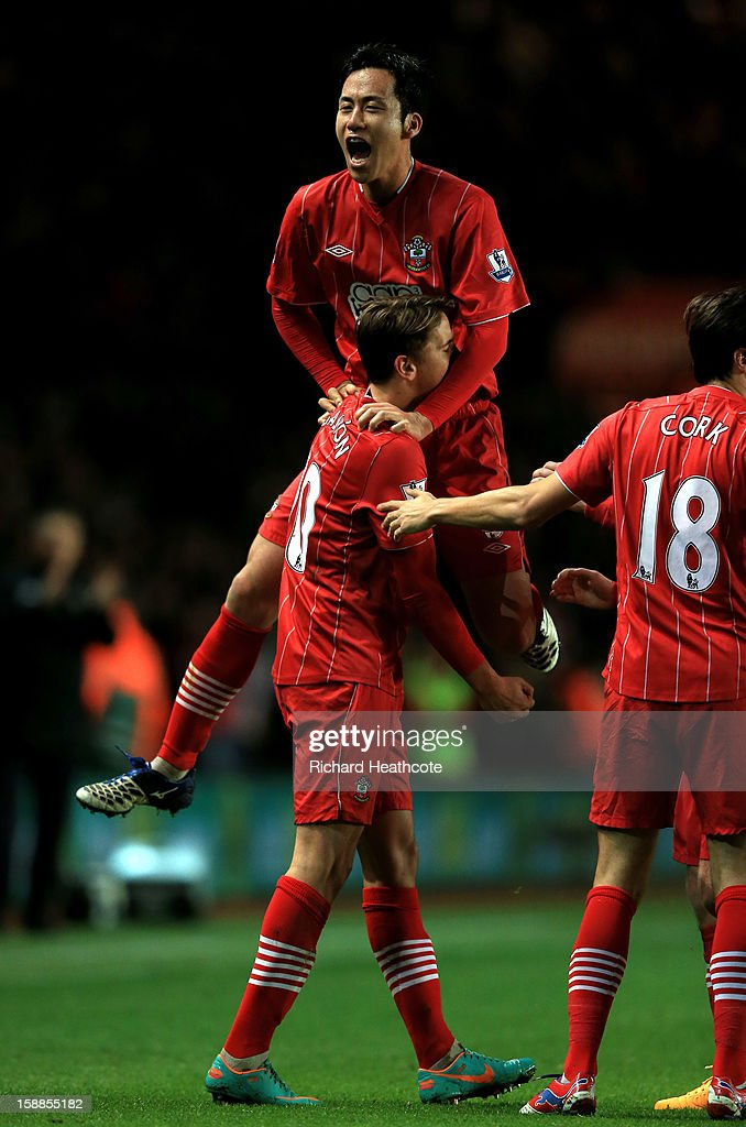 Gaston Ramirez (bottom) of Southampton celebrates with teammate Maya Yoshida after scoring the opening goal during the Barclays Premier league match between Southampton and Arsenal at St Mary's Stadium on January 1, 2013 in Southampton, England.