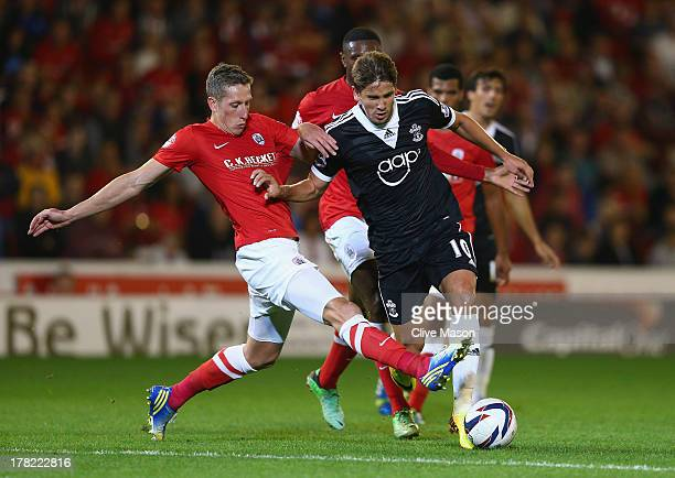 Gaston Ramirez of Southampton is tackled by Jimmy McNulty of Barnsley during the Capital One Cup Second Round match between Barnsley and Southampton...