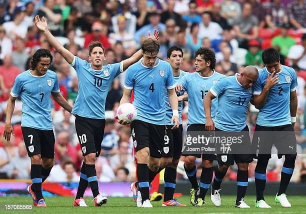 Gaston Ramirez of Uruguay celebrates with his team mates after scoring his team's first goal during the Men's Football first round Group A Match of...
