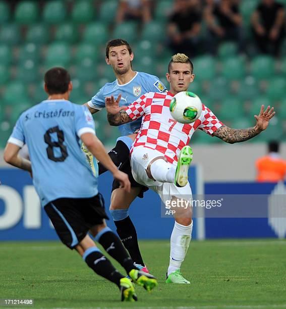 Gaston Silva and Sebastian Christoforo of Uruguay vie for the ball with Marko Livaja of Croatia during a group stage football match between Croatia...