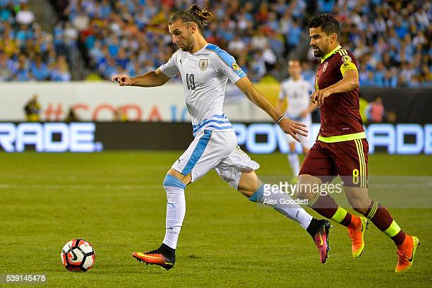 Gaston Silva of Uruguay dribbles past Tomas Rincon of Venezuela during a group C match between Uruguay and Venezuela at Lincoln Financial Field as...