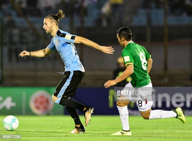 Gaston Silva of Uruguay drives the ball while followed by Diego Bejarano of Bolivial during a match between Uruguay and Bolivia as part of FIFA 2018...