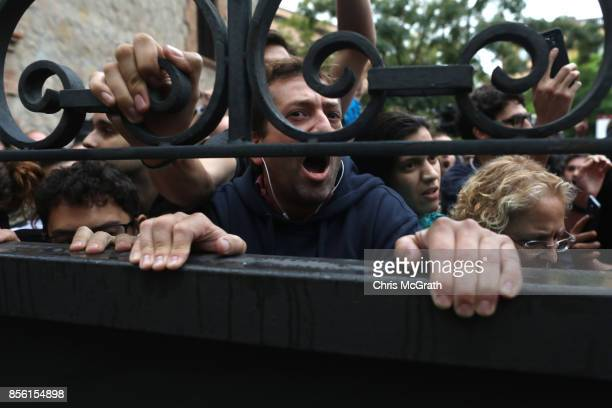 A gate locks people out as police try to control the area where people wait to cast their ballot in the referendum vote at Escola Industrial of...