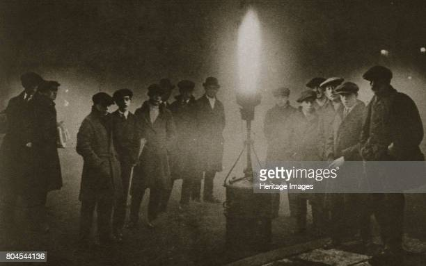 Gathering around an acetylene flare at a traffic control point in the fog early 20th century