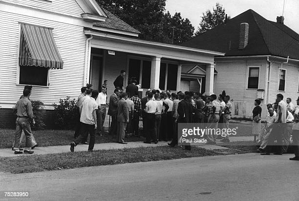 A gathering on a suburban street in Little Rock Arkansas where the the first school desegregation in the US at Central High School is being enforced...