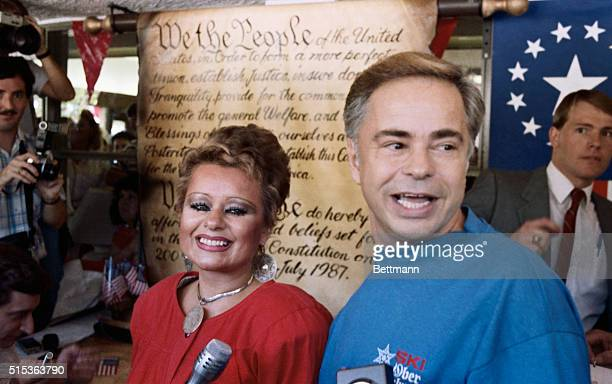 Jim Bakker founder of the PTL television ministry and his wife Tammy Faye stand in front of a replica of the Constitution after signing a scroll to...