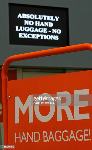 An Easyjet airlines sign promoting their increased baggage allowance is seen in front of security warnings on screen that hand baggage allowance has...