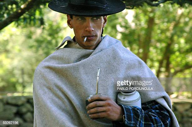 A gaucho holds a thermos bottle and 'mate' during a midmorning break at estancia Parada Arteaga 158 km from Montevideo in Florida Uruguay 21 June...