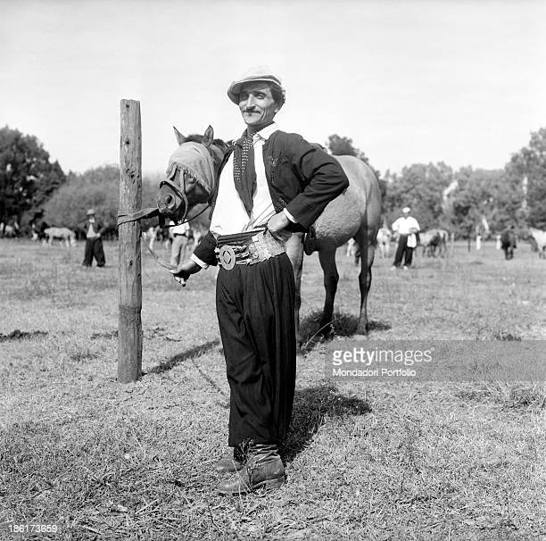 A gaucho poses beside his horse gauchos are the typical South American cattlemen the equivalent of North American cowboys found in the pampas in...