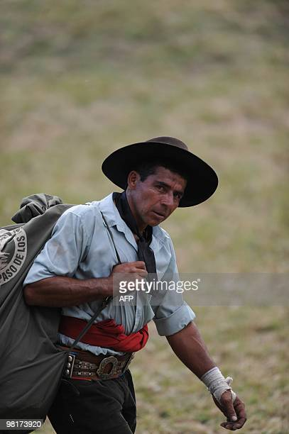 A gaucho walks with his tack after riding a colt during a rodeo of the Patria Grande festival in Montevideo on March 31 2010 The Prado Criolla Week...