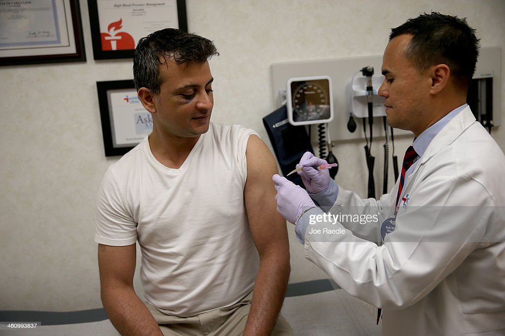 Gautam Gupta receives an influenza shot from Nurse Practitioner Ray Grigorio in the MinuteClinic at the CVS/pharmacy on January 6 2014 in Fort...