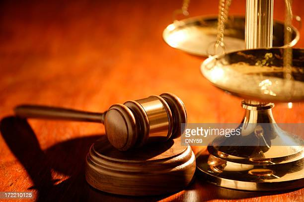 Gavel and scale of justice on wood table