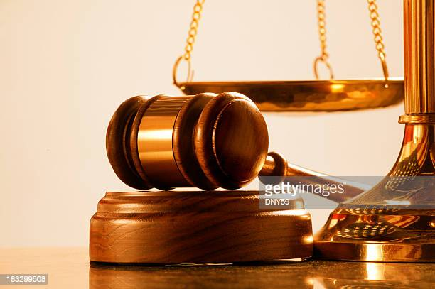 Gavel and sound block at base of brass scale of justice