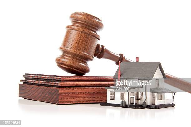Gavel and sound block behind a model house on white