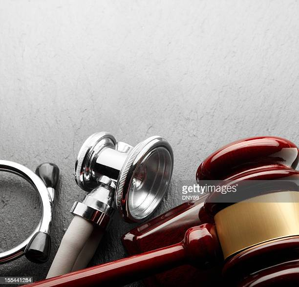 Gavel and stethoscope on black slate background