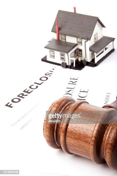 Gavel, foreclosure notice and  model house on white
