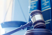 A gavel rests on its sounding block with a several law books and a justice scale out of focus in the background.  A cool blue cast dominates the scene.