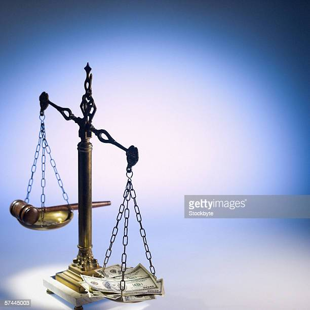 A gavel on one end of a scale and money on the other