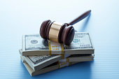 This is a close up color photograph of a wooden gavel with a metal band sitting on a large stack of American US currency money. The background is high key allowing for copy space and text.
