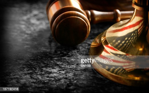 Gavel sitting at base of justice scale with reflection of flag
