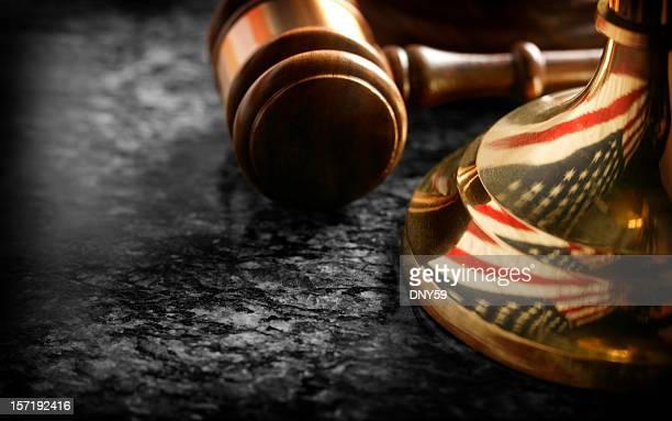 Marteau de juge assis à la base de la justice d'envergure avec reflet de drapeau