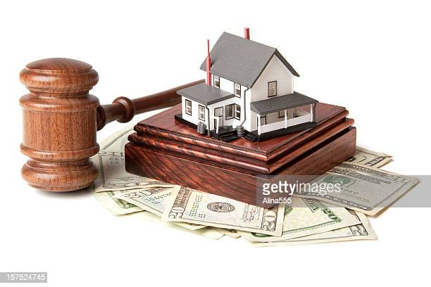 Gavel, sound block and money with model house on white