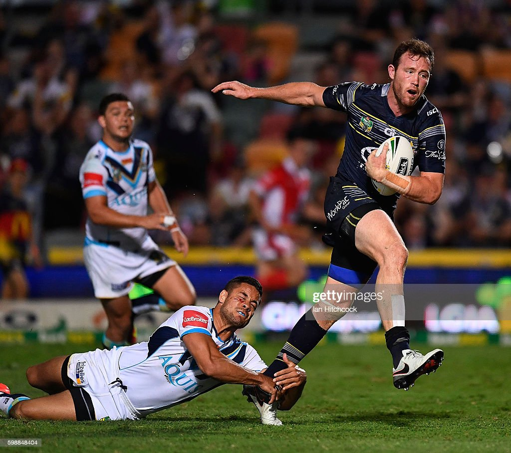 Gavin Cooper of the Cowboys beats the tackle of Jarryd Hayne of the Titans to scores a try during the round 26 NRL match between the North Queensland Cowboys and the Gold Coast Titans at 1300SMILES Stadium on September 3, 2016 in Townsville, Australia.
