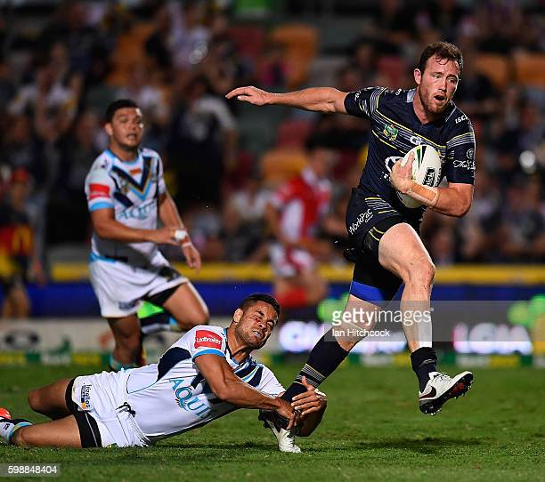 Gavin Cooper of the Cowboys beats the tackle of Jarryd Hayne of the Titans to scores a try during the round 26 NRL match between the North Queensland...