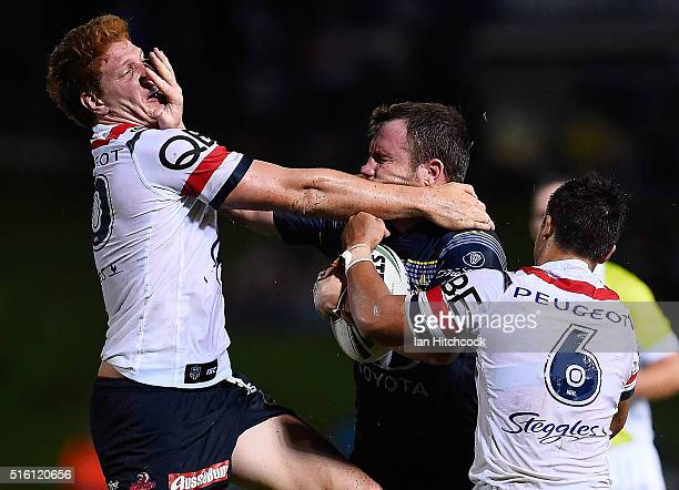 Gavin Cooper of the Cowboys fends Dylan Napa of the Roosters during the round three NRL match between the North Queensland Cowboys and the Sydney...